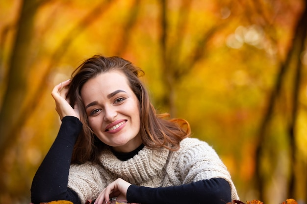 Изящная темноволосая женщина смотрит в камеру и опирается головой на руки на фоне осеннего леса. крупный план