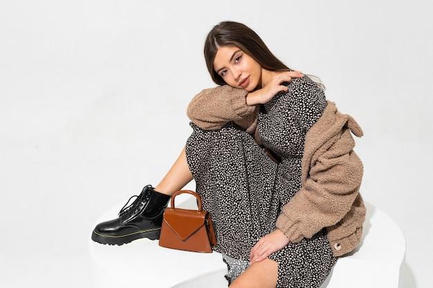 Изящная европейская женщина в зимней шубе и стильном сидении платья. ношение ботинок из черной кожи.