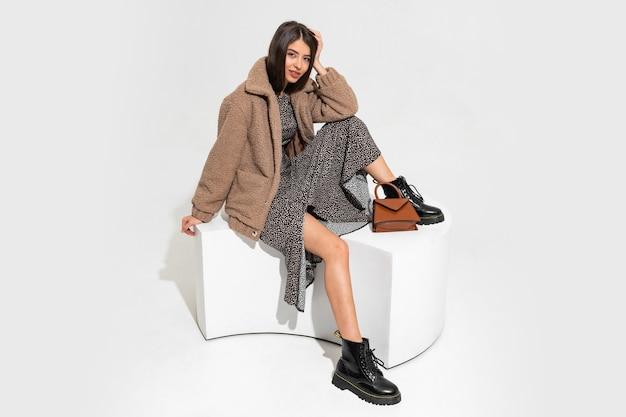 Graziosa donna europea in pelliccia invernale e abito elegante seduto. indossare stivaletti in pelle nera.