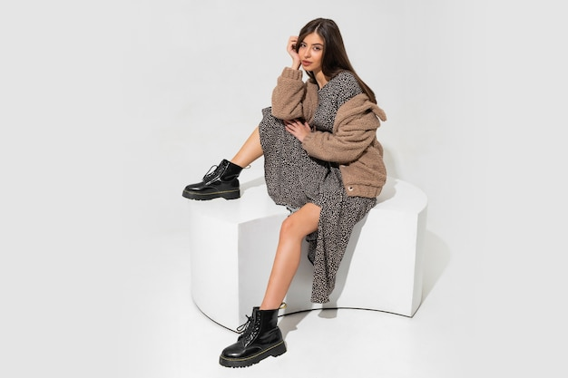 Graceful european woman in winter fur coat and stylish dress sitting. wearing ankle boot in black leather.