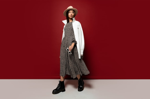 Graceful fashion model in trendy hat and autumn white jacket posing.
