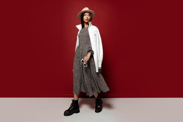 Graziosa modella in cappello alla moda e giacca bianca autunnale in posa.