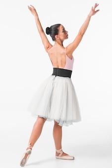 Graceful female ballerina dancer dancing against white backdrop