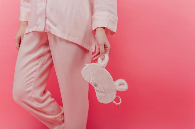 Изящная женская модель в уютном ночном костюме с маской для сна. на фотографии в помещении женщина в розовой хлопковой пижаме стоит с маской для глаз в руке.