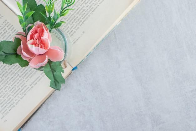 白い背景の上の本の瓶の中の優雅な花。高品質の写真