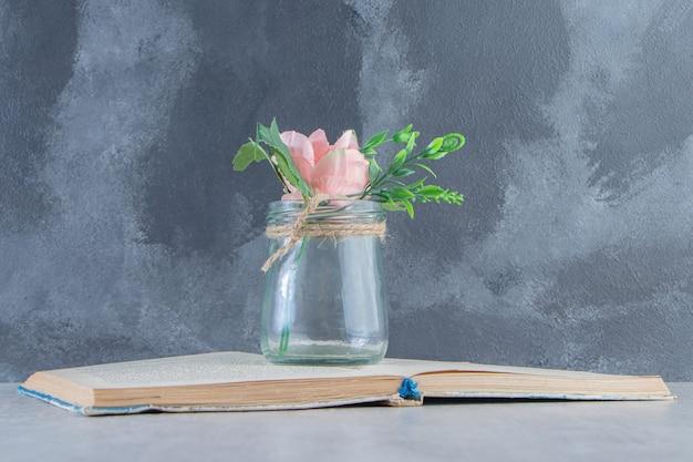 Изящные цветы в банке на книге, на белом фоне.