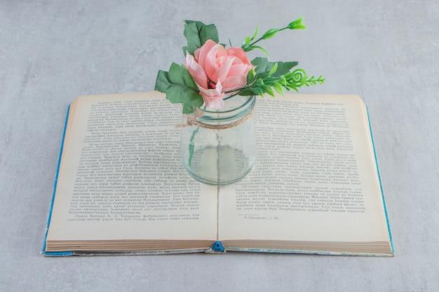 Изящные цветы в банке на книге, на белом столе.
