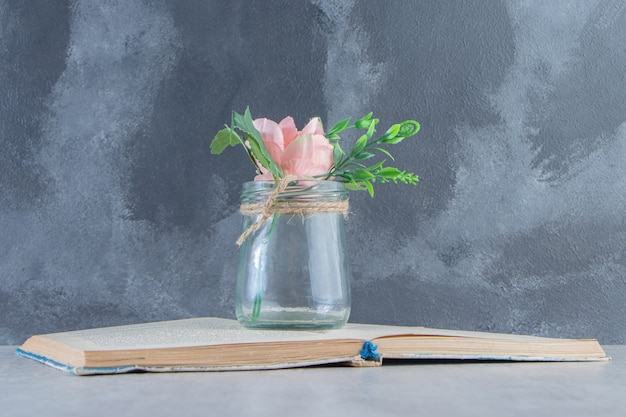 Graceful flowers in a jar on the book , on the white background.