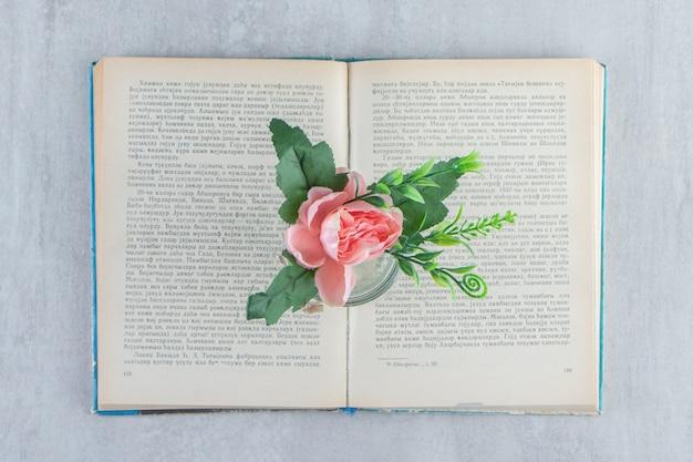 Graziosi fiori in un barattolo sul libro, sul tavolo bianco.