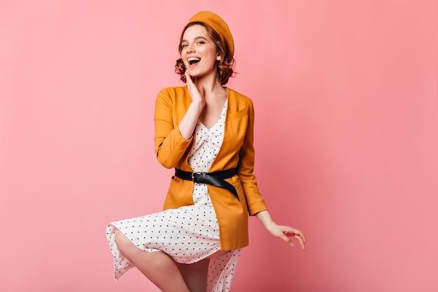 ピンクの背景で踊る優雅なフランスの女の子。黄色い服を着たインスピレーションを得た巻き毛の女性のスタジオショット。