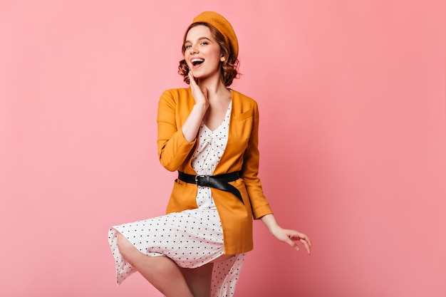 Graceful french girl dancing on pink background. studio shot of inspired curly woman in yellow clothes.