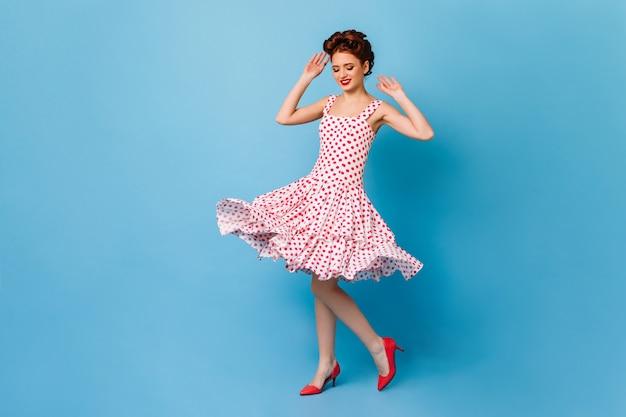 青い空間で楽しんでいるピンナップヘアスタイルの優雅な生姜の女性。笑顔で踊るヨーロッパの女の子の全身像。