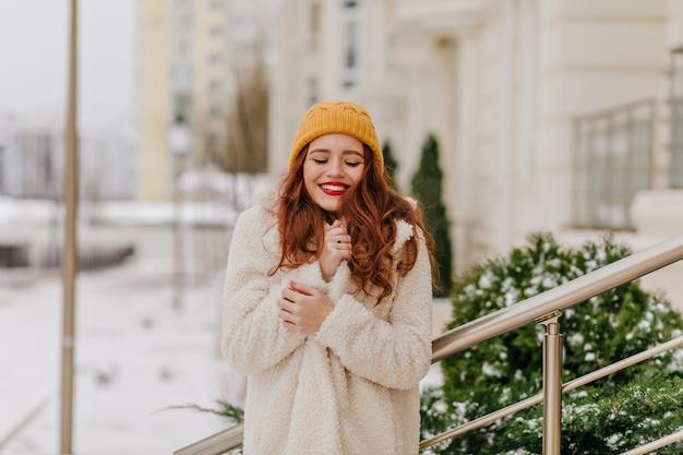 겨울에 포즈 우아한 생강 젊은 여자. 미소와 함께 거리에 서있는 세련 된 코트에서 영감 된 백인 여자.