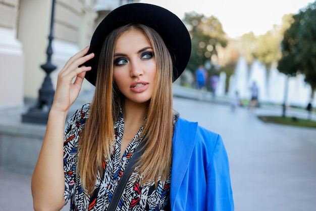 Graceful   girl in elegant  autumn outfit walking while holidays in europe. stylish leather bag.  blue jacket and black hat.