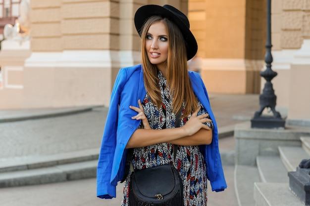 Изящная девушка в элегантном осеннем наряде гуляет во время отпуска в европе. стильная кожаная сумка. синий пиджак и черная шляпа.