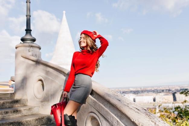 Изящная девушка в серой юбке держит красный рюкзак и улыбается с закрытыми глазами
