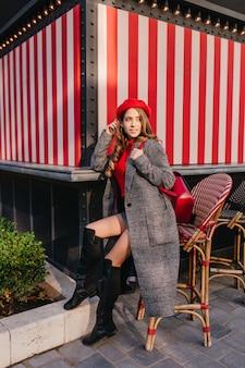 Изящная девушка в длинном твидовом пальто сидит на стуле на улице и ждет кого-то