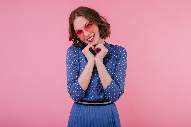 恥ずかしがり屋の誠実な笑顔でポーズをとるピンクのサングラスの優雅な女の子。パステルカラーの壁に分離された青い服装の魅力的な巻き毛の女性の屋内写真。