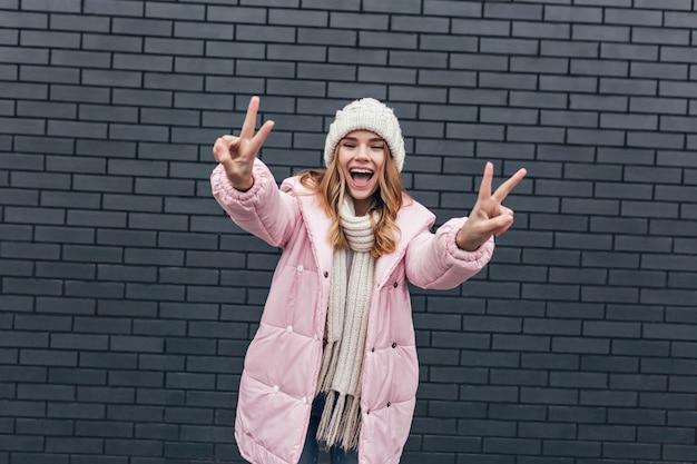 アウトドアを楽しんでいるスタイリッシュな冬のジャケットの優雅な女の子。壮大な金髪の女性の写真は白いニット帽をかぶっています。