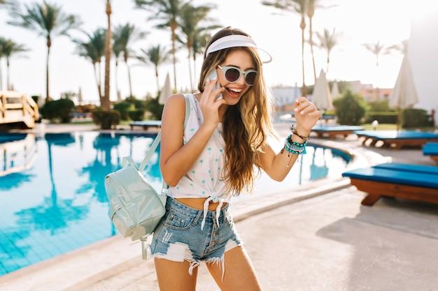 サングラスと帽子のトレンディなバックパックで優雅な女の子は、架台のベッドで日光浴するためにプールに来ました