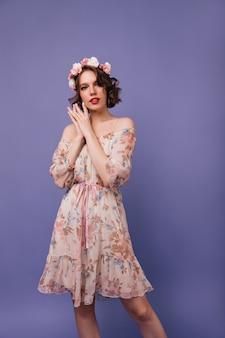 Изящная девушка в модном платье стоя. заинтересованная женщина с цветами в вьющихся волосах позирует.