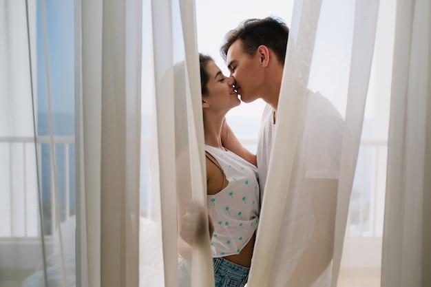 ライトカーテンの後ろに隠れているブルネットのボーイフレンドに優しくキスをする白いタンクトップの優雅な女の子。一緒に楽しんでいるバルコニーで一緒に時間を過ごすロマンチックな若いカップルの肖像。