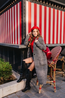 Graziosa ragazza in un lungo cappotto di tweed seduto su una sedia per strada e in attesa di qualcuno