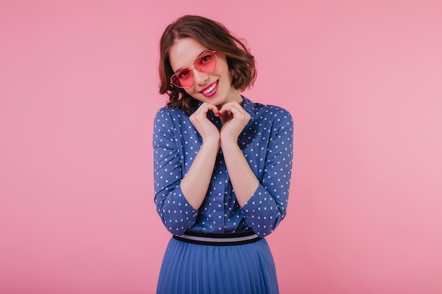 Graceful girl in pink sunglasses posing with shy sincere smile. indoor photo of winsome curly lady in blue attire isolated on pastel wall.