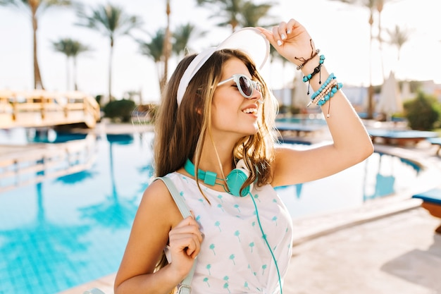 Graziosa ragazza in occhiali da sole e cappello con zaino alla moda è venuta in piscina per prendere il sole sul letto a cavalletto