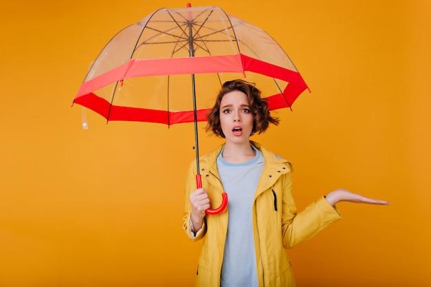 Graceful girl wears stylish autumn coat standing under parasol. studio portrait of upset caucasian female model posing with umbrella on yellow wall.