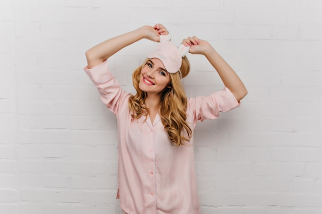 ピンクのシルクのナイトスーツでポーズをとるウェーブのかかった髪の優雅な女の子。朝に踊るアイマスクのポジティブな若い女性。