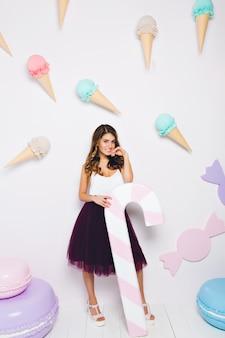 Изящная радостная девушка с большой игрушечной конфетой ждет вечеринки, стоя рядом с большими красочными миндальным печеньем. портрет элегантной модной женщины в полный рост в пышной юбке и белой майке.