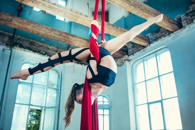 Изящная гимнастка, выполняющая воздушные упражнения на чердаке