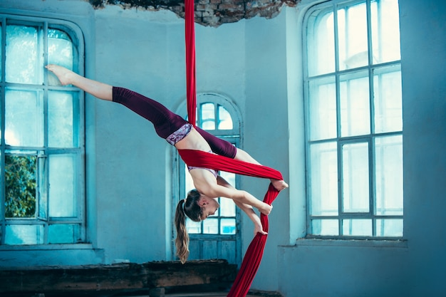 Graceful gymnast performing aerial exercise at loft