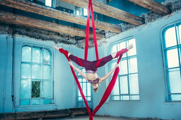 Graziosa ginnasta eseguendo esercizi aerei con tessuti rossi su sfondo blu vecchio loft. giovane ragazza caucasica teenager adatta.