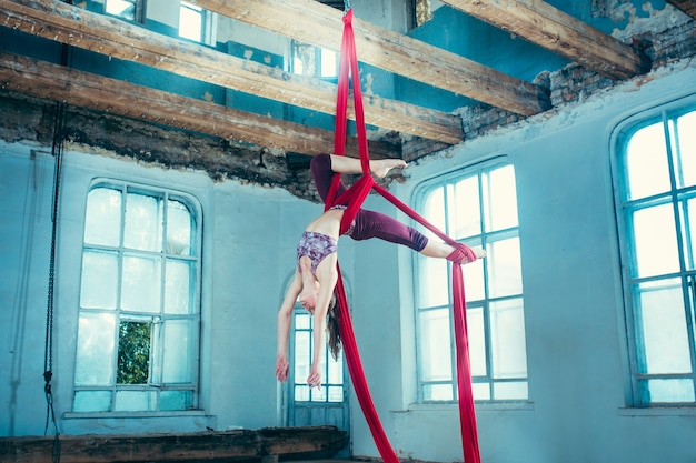 Graceful gymnast performing aerial exercise with red fabrics on blue old loft background.