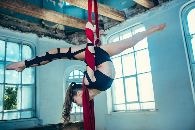 Graceful gymnast performing aerial exercise with red fabrics on blue old loft