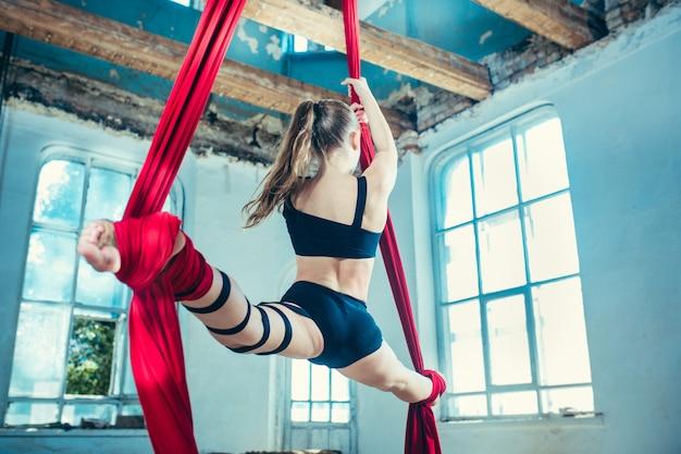 Изящная гимнастка, выполняющая воздушные упражнения с красными тканями на синем старом фоне чердака. молодая предназначенная для подростков кавказская подходящая девушка.