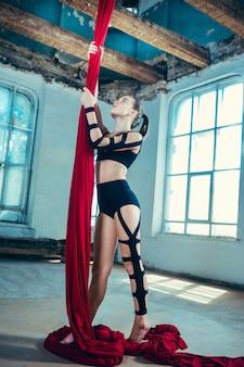Изящная гимнастка выполняет воздушные упражнения с красными тканями на синем старом чердаке