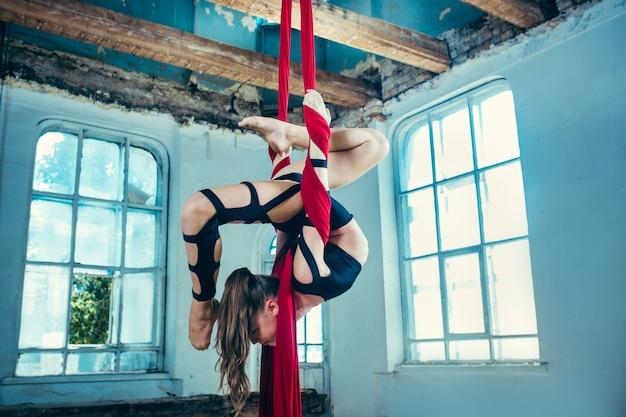 Изящная гимнастка выполняет воздушное упражнение с красными тканями