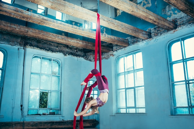 Graceful gymnast performing aerial exercise with red fabrics