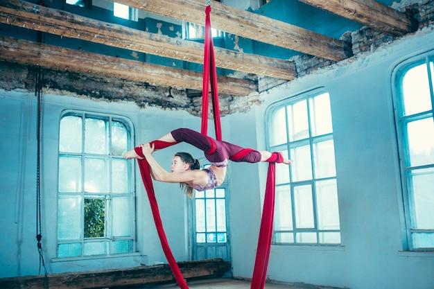 Graziosa ginnasta che esegue esercizi aerei con tessuti rossi