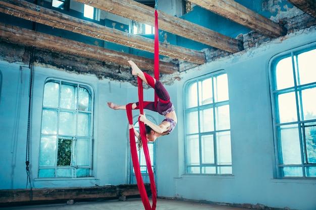 Изящная гимнастка, выполняющая воздушные упражнения
