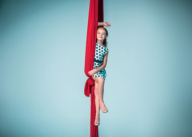 Graceful gymnast sitting with red fabrics