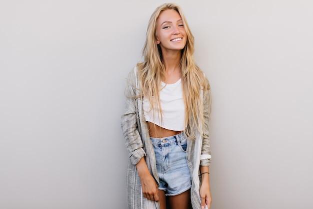 カメラに微笑んで長い髪の優雅な幸せな女性。ポジティブな感情を表現する魅力的なヨーロッパの女性の屋内写真。