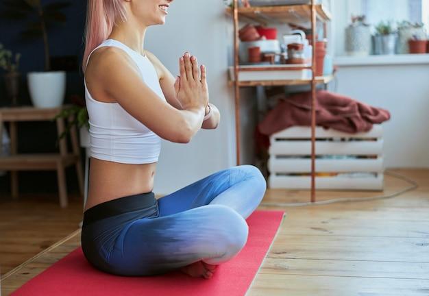 優雅な女性が自宅で蓮華座に座って瞑想クローズアップ側面図