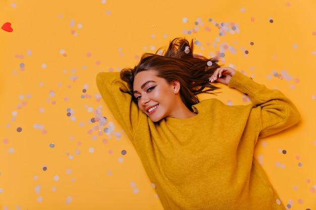Graziosa signora con capelli castani sdraiato sul muro giallo. ritratto ambientale della donna alla moda sensuale in maglione arancione.