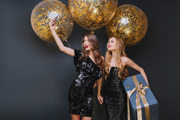 Graceful lady with light-brown hair making selfie with birthday girl. pretty young woman in romantic attire holding present and having fun with friend.