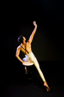 Graceful male ballet dancer stretching in spotlight
