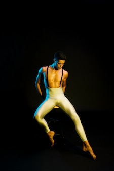 Graceful male ballet performer sitting in spotlight